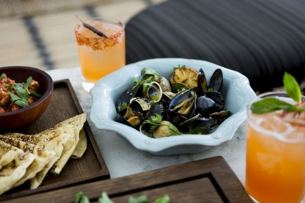 table with bowl with clams, cocktails and salsa