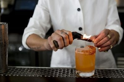cocktail with chilli powder on the rim while bartender roasts chilli pepper with flamethrower